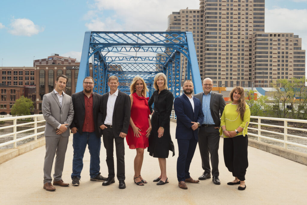 A picture of the Keystone Home Group team on a bridge with a city in the backdrop.